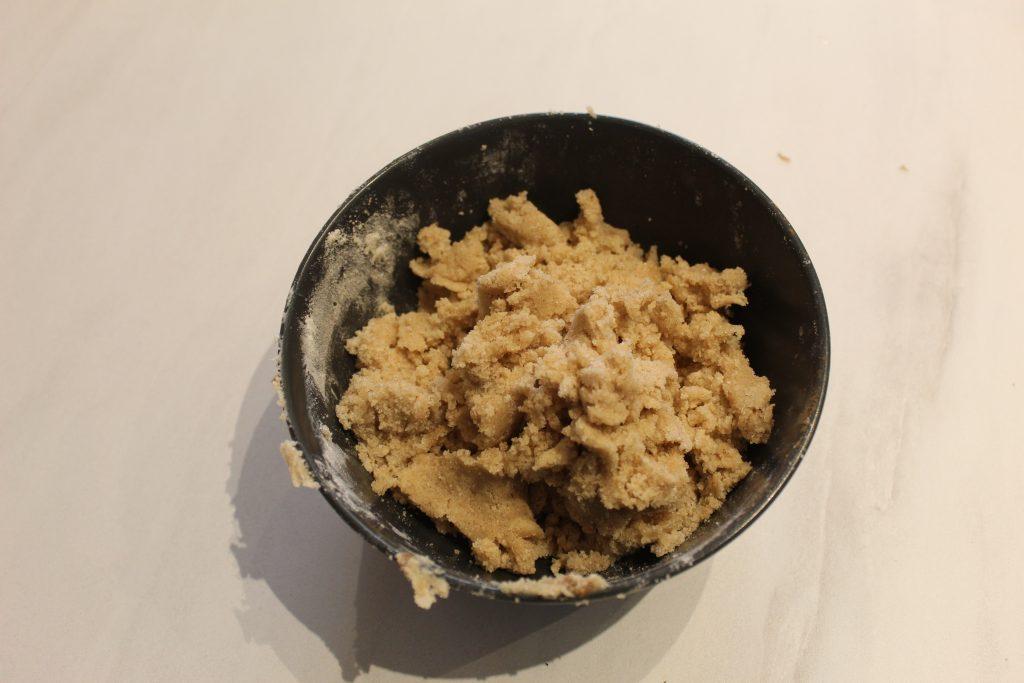 V posodi zmešamo maslo sobne temperature ter žličko cimeta; v drugi posodi zmešamo moko in sladkor; in na koncu vse skupaj z roko fino pregnetemo v razpadajočo zmes..
